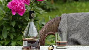 Avattu konjakkipullo puutarhan pöydällä.