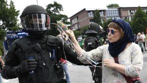 Huivipäinen mielenosoittajanainen osoittaa yksisarvislelulla kohti mellakkapoliisin kypärää.