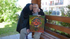 Mies ja nainen istuvat taulu sylissä kerrostalon pihalla