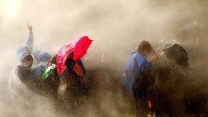 Poliisit kastelevat mielenosoittajia vesitykeillä Hampurissa.