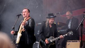 Kolme miesstä soittaa rokkifestivaalilla isolla lavall