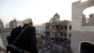 mies katselee raunioita Jemenissä