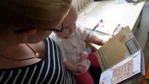 Anna-Johanna Makkonen ja Ada-vauva katsovat kalenteria