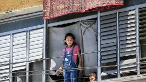 Tyttö ja poika katselevat ikkunasta kadulle.