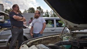 Itäautoharrastaja Jussi Kulonen ja toinen mies seisovat kahden itäauton välissä huutokaupan katselmuksessa Sallassa.