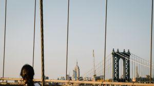 Nainen katsoo New Yorkin Brooklyn Bridgelle Brooklynissa. Takana siintää kaupungin pilvenpiirtäjä, joukossaan Empire State Building.