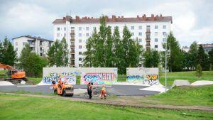 Työmiehiä ja työkoneita Oulun Hollihaan leikkipuistossa, jossa graffitimaalauksia ja taustalla kerrostalo.
