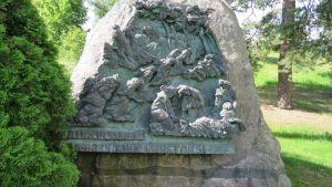 """Luonnonkiveen kiinnitetty kuparireliefi nälkään nääntyvistä ihmisistä. Tekstinä """"Näkävuosien 1866–1868 uhrien muistoksi""""."""