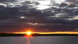 Keskiyön aurinko Lapissa. Yöttömän yön ilmiön voi kokea vain pohjoisella napapiirillä ja sitä korkeammilla leveysasteilla.