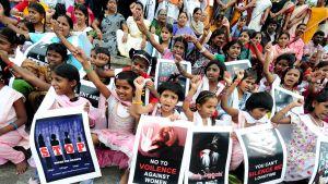 Lapsia istumassa kadulla, kädessä kylttejä, joissa lukee muun muassa No to violence against women.