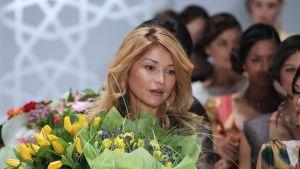 Gulnara Karimova suuri kukkakimppu sylissään. Taustalla seisoo jono muotinäytöksen malleja.