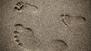 Aikuisen ja lapsen jälkiä hiekassa.