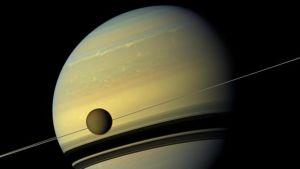 Titan-kuu Saturnuksen kiertoradalla. Kuvassa näkyy myös Saturnuksen renkaita.