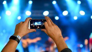 Mies ottaa kännykällä kuvaa Qstockin esiintyjästä.