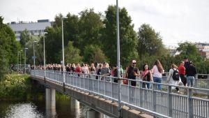 Yleisöä saapumassa Pikisaarensiltaa pitkin Oulun Qstockiin.
