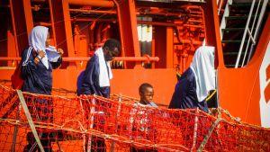 Siirtolaisia kävelee pelastuslautalta maihin.