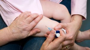Sairaanhoitaja antaa MPR-rokotuksen reiteen vuoden ikäiselle vauvalle.