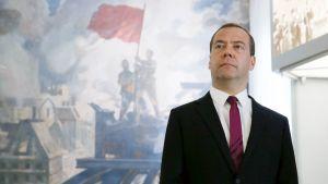 Dmitri Medvedev seisoo seinämaalauksen edessä Smolenskin alueen sotamuseossa ja katsoo kuva-alalla yläoikeaan. Maalauksessa neuvostosotilaat pystyttävät punalippua talon katolle sodasta kärsineessä kaupunkimaisemassa.