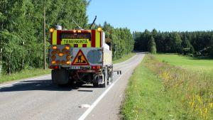 Tiemerkintäauto maalaa maantien reunaviivaa.