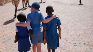 Kolme lasta kävelee kaulakkain lesotholaisessa koulussa.