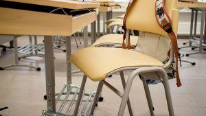 Koulureppu ja tyhjä pulpetti luokkahuoneessa.