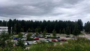 Kouvolan oikeus- ja poliisitalon parkkipaikalla autoja, parkkipaikan takana metsä, jonne sairaalahenke Ratamo-keskus Kouvolassa suunniteltu