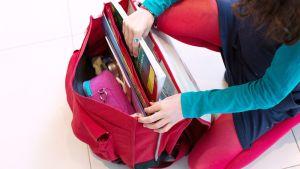 Koululainen pakkaa kirjoja laukkuunsa.