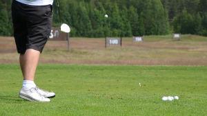Golfaaja lyö palloa harjoitusalueella.