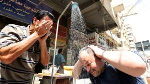Irakilaismiehet vilvoittelivat julkisen suihkun äärellä Bagdadissa 10. kesäkuuta Ramadanin aikaan, jolloin lämpö kohosi yli 40 celciusasteen.