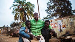 Levottomuuksissa loukkaantunutta miestä kannettiin Kiberan slummissa 12. elokuuta.