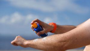 Mies laittaa aurinkorasvaa käsivarrelleen.