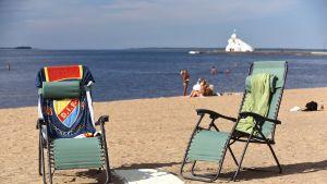 Kaksi aurinkotuolia, joilla pyyhkeet Oulun Nallikarin hiekkarannalla.