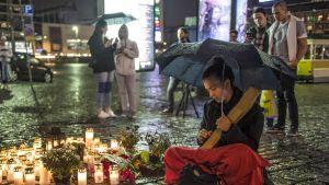 Henkilö soittamassa kanteletta kynttilöiden vieressä kadulla.