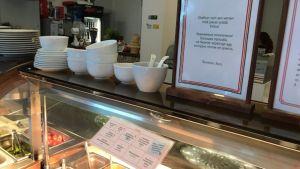 Lounasbuffet ja kyltti, jossa lukee: Otathan vain sen verran mitä jaksat syödä.