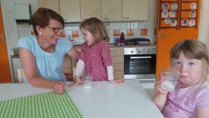 Satu Ruusunen istuu ruokapöydässä hoitolastensa kanssa