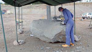 Haalaripukuinen taitelija muovaa teostaan Kempeleen avolouhoksella.
