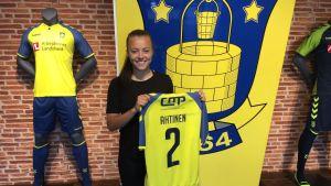 Kuvassa jalkapalloilija Olga Ahtinen pitää kädessään Brøndbyn keltasinistä pelipaitaa.