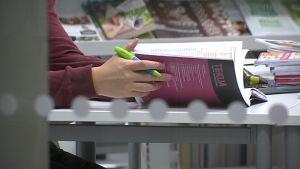 Oppilas selaa koulukirjaa kynä kädessään Kastellin yhtenäiskoulussa Oulussa.