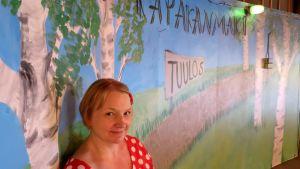 Nuori nainen seisoon seinämaalauksen edessä jossa lukee Kapakanmäki