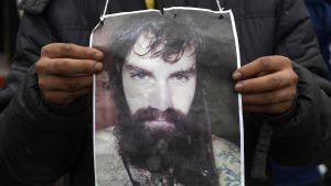 Mies pitelee käsissään julistetta, jossa on Argentiinassa kadoneen Santiago Maldonadon kuva.