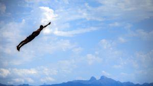 Mies lentää ilmassa laskettuaan 15 metrin vesiliukumäessä Sveitsin alpeilla 26. elokuuta.