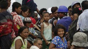 Ihmisiä kuorma-auton lavalla. Joukossa on myös lapsia.