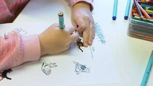 Lapsi värittää väristyskirjaa