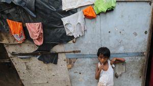 Pikkupoika nojaa hökkelitalon seinään, langalla roikkuu kuivumassa pyykkiä.