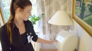 Lähihoitaja Tanja Laine käyttää lääkeannosrobottia.