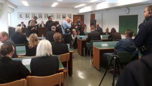Tiedotusvälineet kuvaavat päänsä hupulla peittänyttä Jori Juhani Lasosta käräjäoikeuden istunnon alussa.