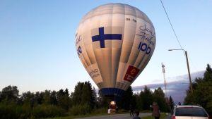Suomi 100 -kuumailmapallo maantiellä.