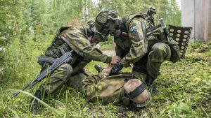 Sotilaspoliisit raudoittaa maalihenkilöä taisteluharjoituksessa.