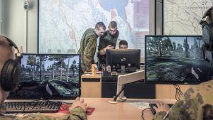 Varusmiehet harjoittelevat sotasimulaattorilla ja luutnantti kouluttaa.
