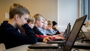 Lintumetsän koulun 8D oppilaita tietokoneilla